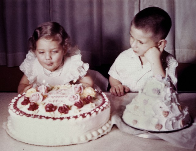 Brother watches his sister blow out candles on birthday cake, ca. 1956